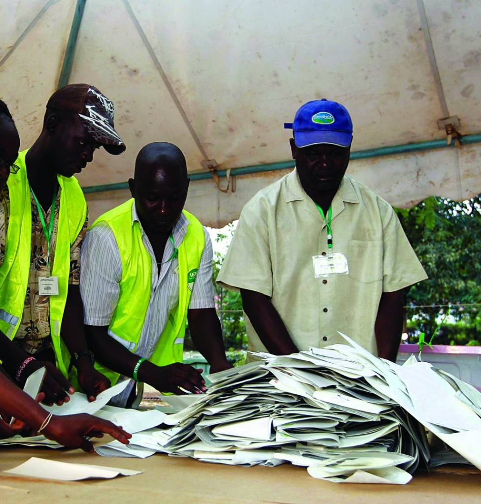 Officials from the Independent Electoral and Boundaries Commission (IEBC) sort out ballot papers after voting closes for presidential and parliamentary elections in Kisumu, 350 km (218 miles) west of the capital Nairobi Monday. (REUTERS/Thomas Mukoya)