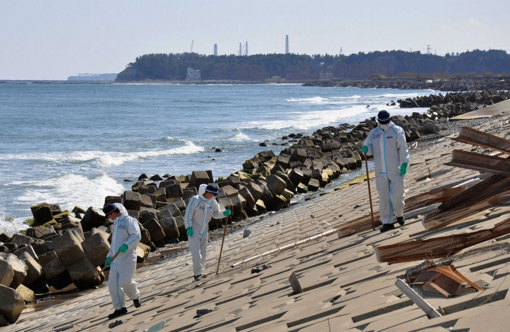 Police officers in protective gear search for missing of the earthquake and tsunami, as Fukushima Daiichi nuclear power plant is background along the coast side in Namie town, inside no-go zone around Fukushima Prefecture. (REUTERS/Kyodo)