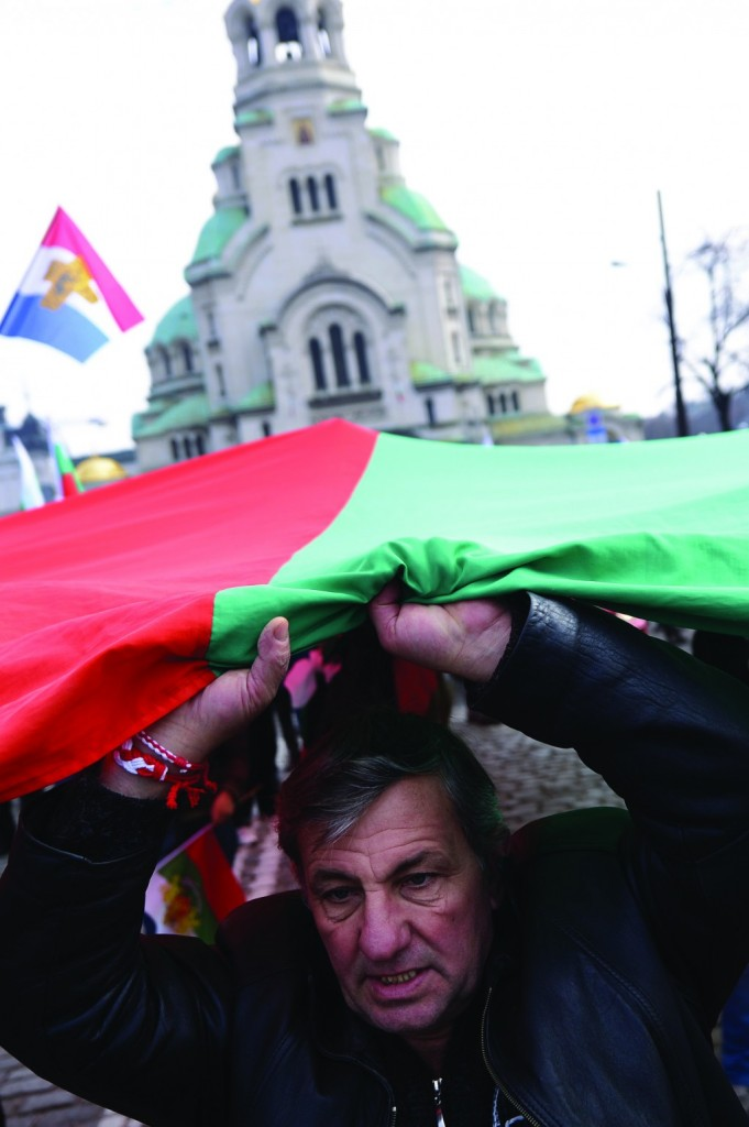 A protester waves a Bulgarian national flag during an anti-monopoly protest in Sofia on Sunday. (AFP Photo / Dimitar Dilkoff)