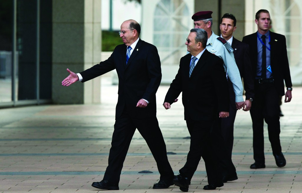 Incoming Israeli Defense Minister Moshe Yaalon (L) and outgoing Defense Minister Ehud Barak walk together during an official changeover ceremony at the Defense Ministry in Tel Aviv on Tuesday. (REUTERS)