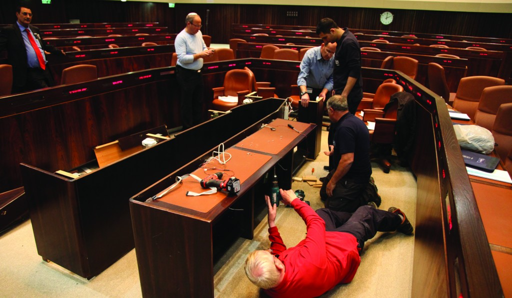 A smaller government means a smaller government table in the Knesset plenum. Carpenters are at work on Sunday implementing the decision. (Flash90)