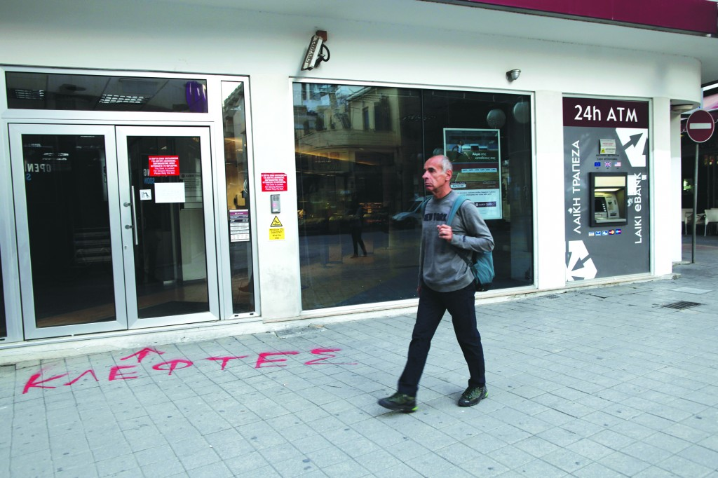 """At the entrance of a closed Laiki Bank graffiti sprayed on the pavement reads in Greek """"thieves"""" as a man walks in capital Nicosia, Cyprus, Wednesday. (AP Photo/Petros Giannakouris)"""