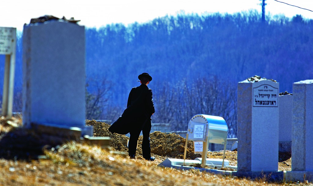"""A person walks towards the graves of Reb Nachman and Mrs. Raizy Glauber, z""""l, at the cemetery in Kiryas Joel, New York, Monday. (APPhoto/Craig Ruttle)"""