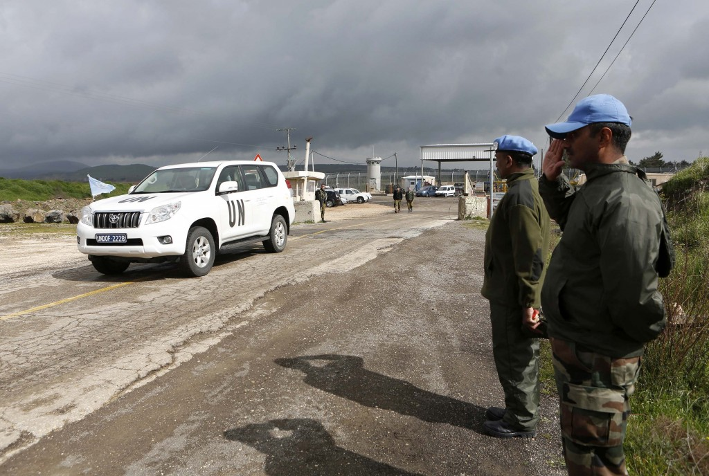 India's United Nations peacekeepers salute as a U.N. vehicle crosses from Syria into Israel at the Kuneitra border crossing on the Golan Heights Tuesday. (REUTERS/Baz Ratner)