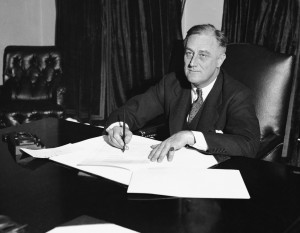 """At a desk in the Cabinet room, President Franklin D. Roosevelt signs the Cullen-Harrison Act, or """"Beer Bill,"""" the first relaxation of the Volstead Act in all the years of Prohibition, on March 22, 1933, in Washington."""