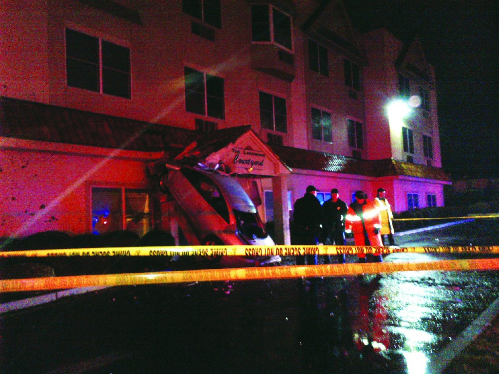 A car driven by a drunk driver lays upturned against the Lakewood Courtyard assisted-living home in the early hours of Tuesday morning. (Meyer Rosenbaum/News Breakers)