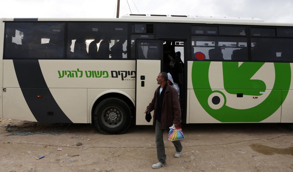 Workers disembark a Palestinian bus before crossing through Israel's Eyal checkpoint as they return to a crossing near Qalqilya on Monday. (REUTERS)