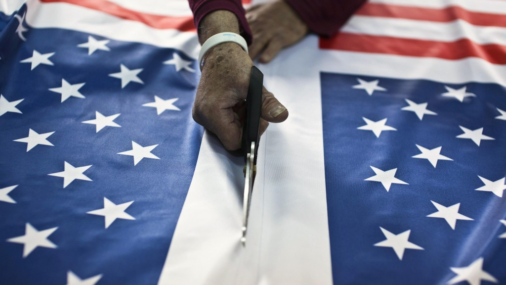 A worker at a factory in Kfar Saba cuts fabric printed with U.S. flags ordered ahead of President Obama's visit to Israel. It was the most work the factory has had since Egyptian President Anwar Sadat visited Israel in 1977, owner Avi Marom said on Tuesday. (REUTERS )