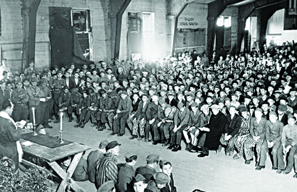 Rabbi Hershel Schacter conducting services at the liberated Buchenwald concentration camp in 1945.