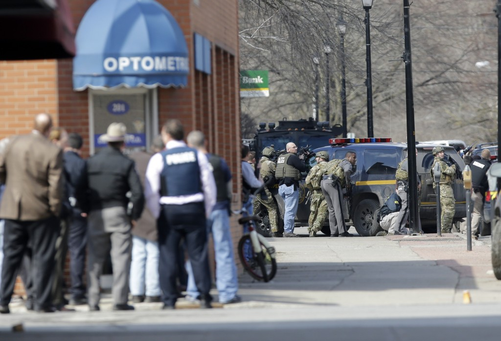 Law enforcement officers take cover along Main Street in Herkimer, N.Y. as the search for a suspect in two shootings that killed four goes on. (AP Photo/Mike Groll)