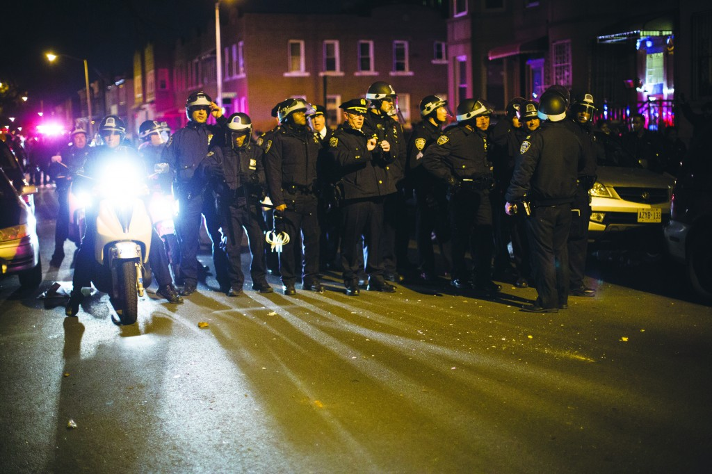 "Police officers regroup in the predawn hours Thursday in Flatbush after a volley of glass bottles was thrown at them from a group of demonstrators protesting the death of Kimani ""Kiki"" Gray. (AP Photo/John Minchillo)"