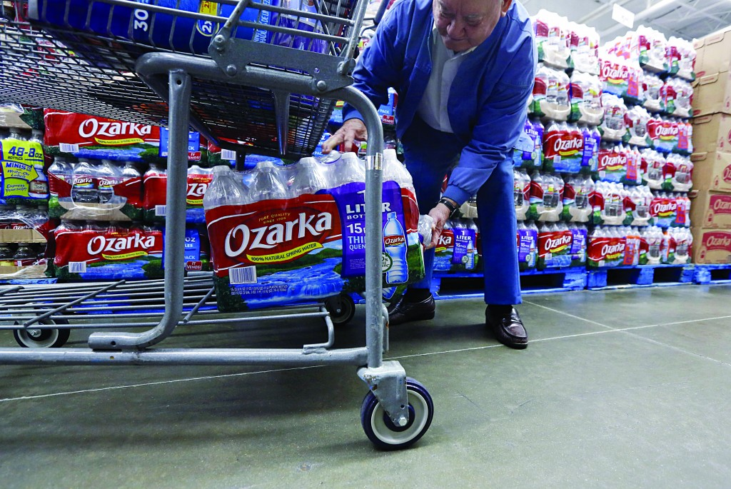 Walter Pugh, 83, of Belzoni, Miss., loads a case of his bottled water into his shopping cart last Tuesday. (AP Photo/Rogelio V. Solis)