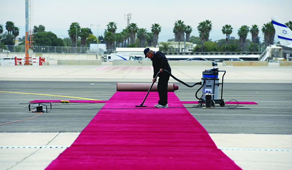 A worker vacuums a red carpet at Ben Gurion International Airport in preparation for the welcome ceremony that will take place Wednesday after Air Force 1 lands with President Obama on board. (Kobi Gideon / GPO/Flash90)
