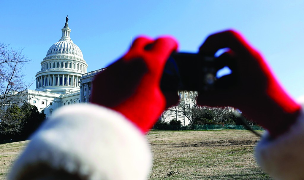 A visitor takes a photo of the U.S. Capitol in Washington Tuesday. (REUTERS/Kevin Lamarque)
