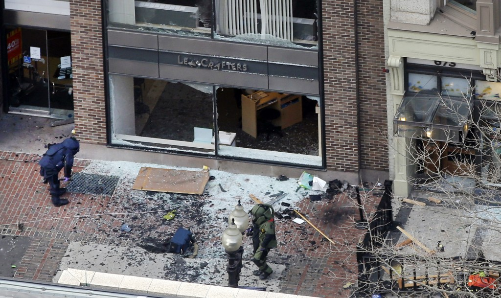 One of the blast sites on Boylston Street is investigated by two people in protective suits in the wake of two blasts in Boston Monday, April 15. (AP Photo/Elise Amendola)