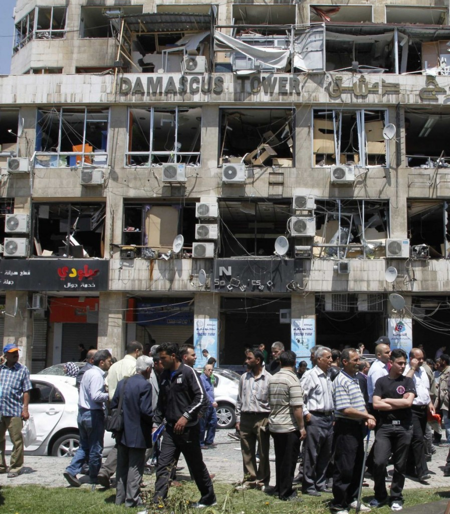 People stand on a street lined with a damaged building and destroyed cars after a blast at Marjeh Square in Damascus Tuesday. (REUTERS/Khaled al-Hariri)