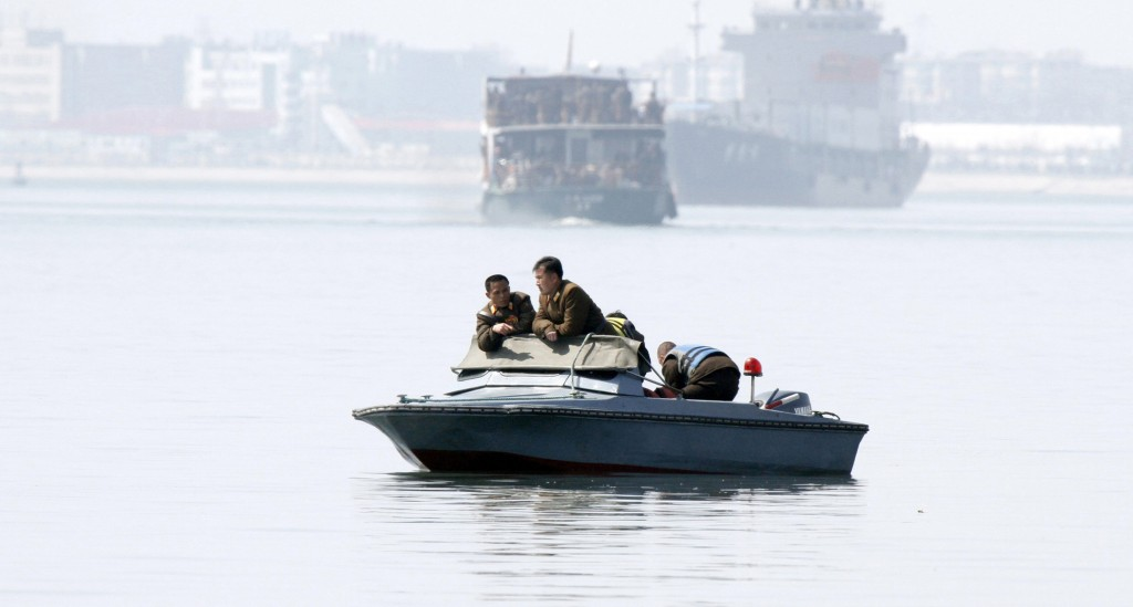 North Korea soldiers lean in a boat on Yalu River, near the North Korean town of Sinuiju, opposite the Chinese border city of Dandong, Wednesday. Chinese authorities in the northeastern city of Dandong have told tour agencies to halt overland tourism into North Korea. (REUTERS/Jacky Chen)