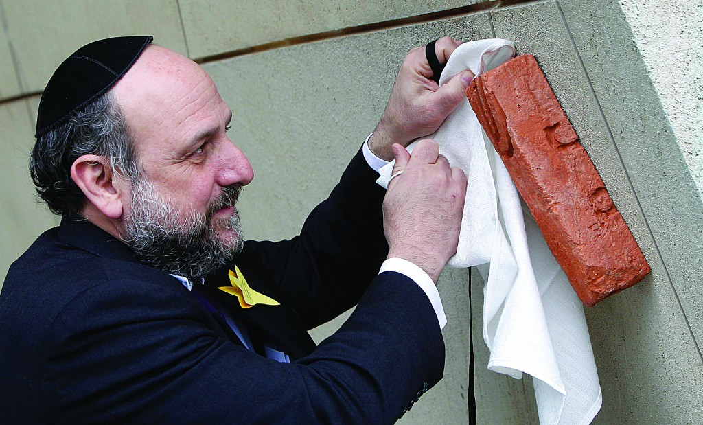 Poland's Chief Rabbi, Michael Schudrich, unveils a mezuzah at the entrance of the Museum of the History of Polish Jews in Warsaw, Poland. (AP Photo/Czarek Sokolowski)