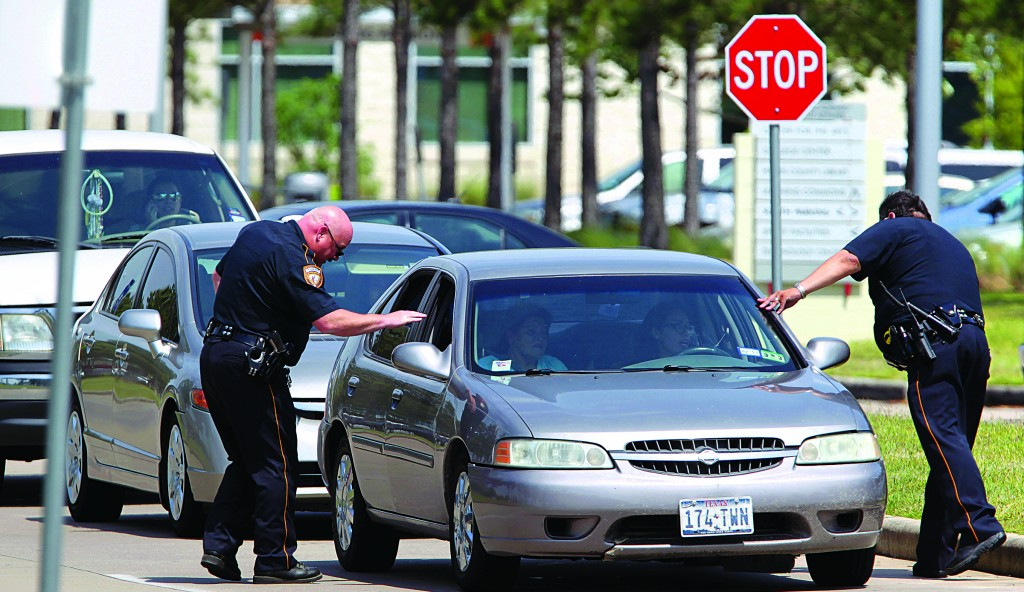 Harris County Sheriff's Deputies check vehicles leaving Lone Star College's Cypress-Fairbanks campus Tuesday in Cypress, Texas. (AP Photo/Houston Chronicle, James Nielse)