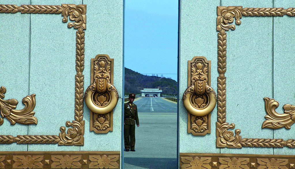 A North Korean soldier guarding the entrance to Pyongyang's Kumsusan mausoleum, where the bodies of the late leaders Kim Il Sung and Kim Jong Il lie embalmed, looks back through the doors of the main gate Monday. North Koreans turned out on Monday to mark the 101st birthday of Kim Il Sung. (AP Photo/David Guttenfelder)