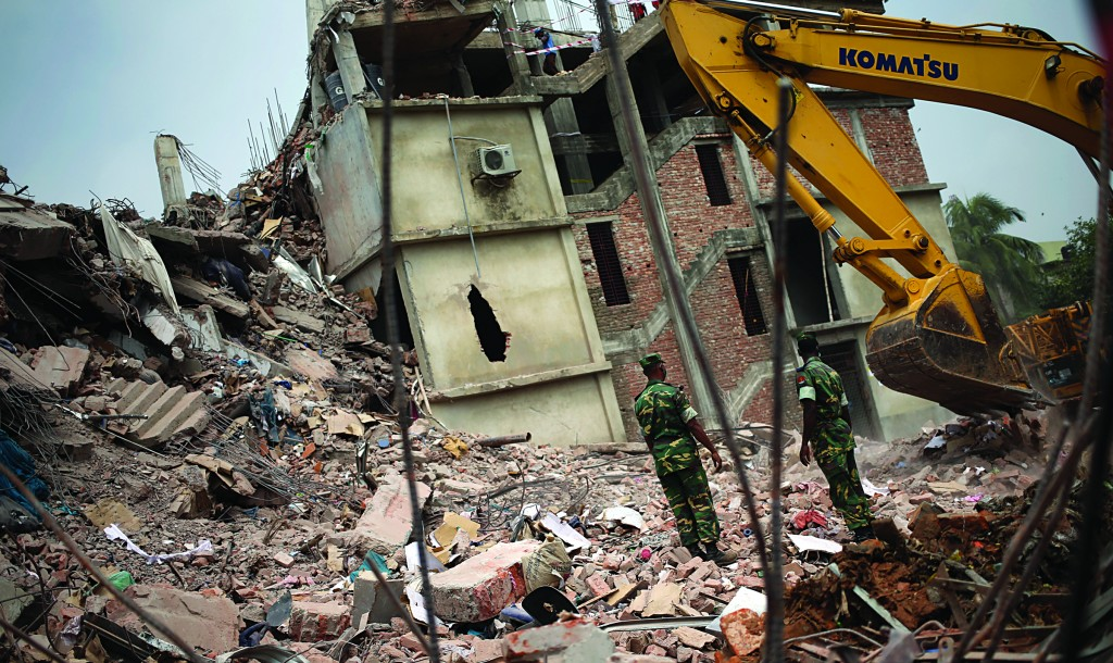 Army personnel watch as workers toil in the collapsed garment factory building, Tuesday, near Dhaka, Bangladesh. (AP Photo/Wong Maye-E)