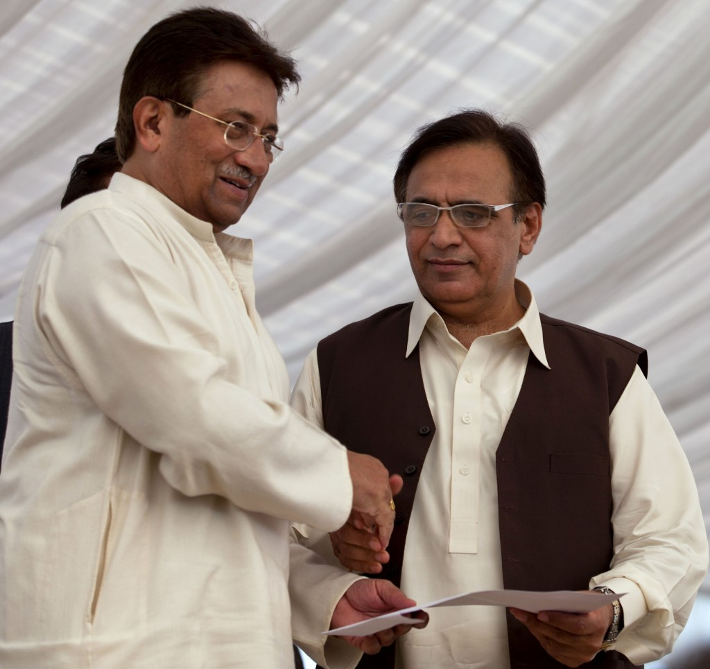 Pakistan's former President and military ruler Pervez Musharraf, left, shakes hands with Mohammad Amjad after he announces his party manifesto at his residence in Islamabad, Pakistan, Monday. (AP Photo/B.K. Bangash)