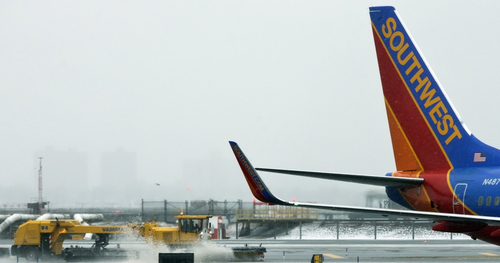 In this Feb. 8, 2013 file photo, grounds crews clear the runway as snow falls at LaGuardia Airport in New York. Airlines are struggling this year to get planes to the gate on time. (AP Photo/Frank Franklin II, File)
