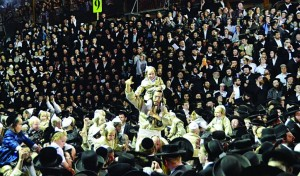 A father and son rejoice during the dancing following the hadlakah of the Toldos Aharon chassidim. (Aharon Baruch Leibow)