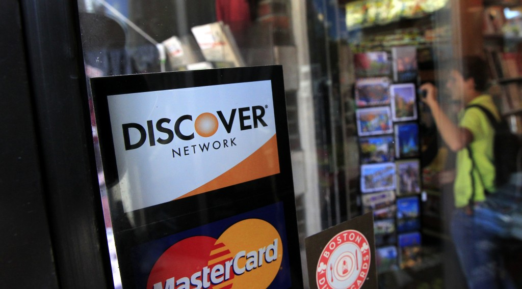 A Discover logo is adhered to a window at the entrance of a shop in Cambridge, Mass. (AP Photo/Steven Senne, File)