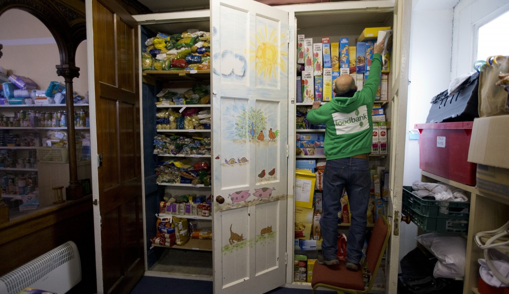 In this photo taken Friday, April 5, a volunteer reaches up to put a box of cereal on a shelf at a food bank in the West Norwood area of London. (AP Photo/Matt Dunham)