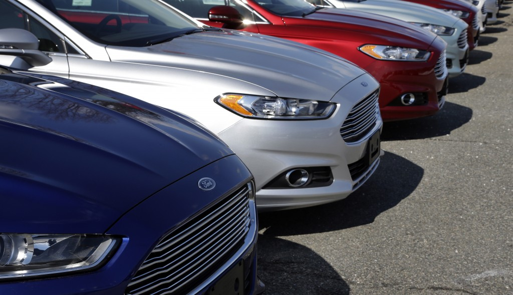 In this March 20, 2013 photo, a row of Ford Fusion sedans sit in a lot at a Ford dealership in, Norwood, Mass. General Motors Co. and Ford Motor Co. have agreed Monday, to jointly design nine- and 10-speed automatic transmissions for cars and trucks. The companies will build the transmissions separately. (AP Photo/Steven Senne)