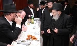 Harav Moshe Wolfson, Rav of Beis Medrash Emunas Yisroel and Mashgiach of Yeshivah Torah Vodaath, gives a check outside the hall at the Bonei Olam dinner.