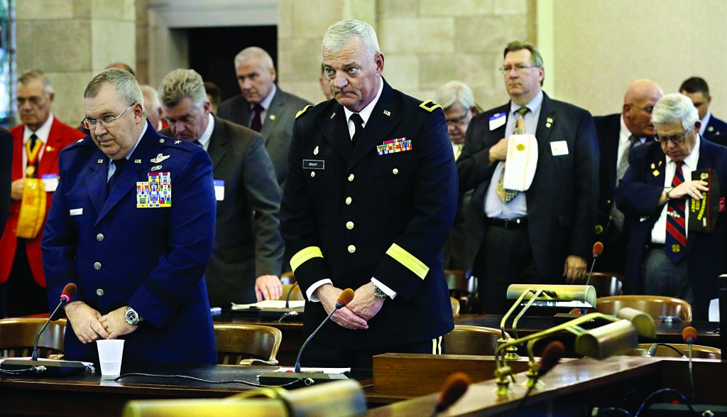 Acting Adjutant General of the Department of Military and Veteran Affairs Brigadier General Michael L. Cunniff (L) and Brigadier General James J. Grant (C), Director, Joint Staff to the Adjutant General of New Jersey, pause with others at the Statehouse in Trenton on Wednesday for a moment of silence for the victims of the bombings in Boston. (AP Photo/Mel Evans)