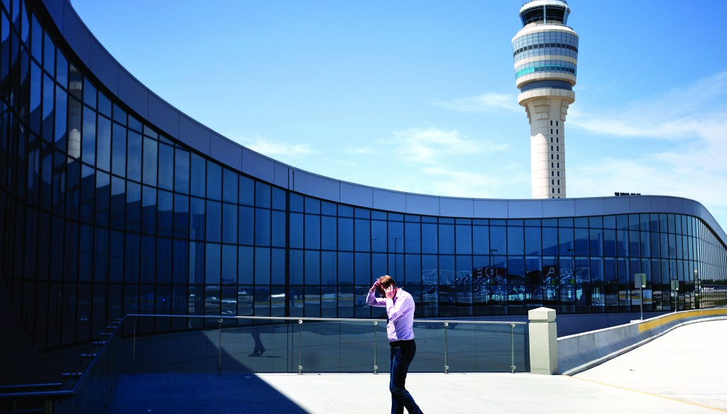 The control tower rises in the background as a passenger paces while on the phone outside the international terminal at Hartsfield-Jackson Airport in Atlanta, Friday. (AP Photo/David Goldman)