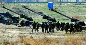 "South Korean soldiers of an artillery unit walk past 155mm Towed Howitzers during an artillery drill as part of the annual joint military exercise ""Foal Eagle"" by the U.S. and South Korea, near the demilitarized zone (DMZ) which separates the two Koreas, in Goseong Tuesday. (REUTERS/Kim Hong-Ji)"