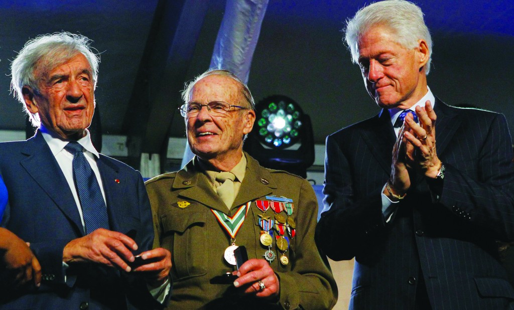 Former President Bill Clinton (R) and Holocaust Museum Founding Chairman Elie Wiesel (L) attend ceremonies commemorating the 20th anniversary of the museum in Washington Monday. World War II veteran and concentration camp liberator Scottie Ooton (C) and Wiesel received commendation medals during the ceremony. (REUTERS/Gary Cameron)