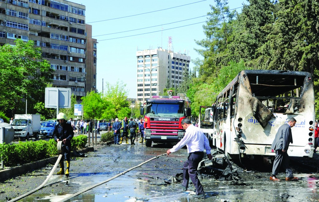 Syrian firefighters extinguishing burning cars after a car bomb exploded in the capital's western neighborhood of Mazzeh, in Damascus, Syria, Monday. (AP Photo/SANA)