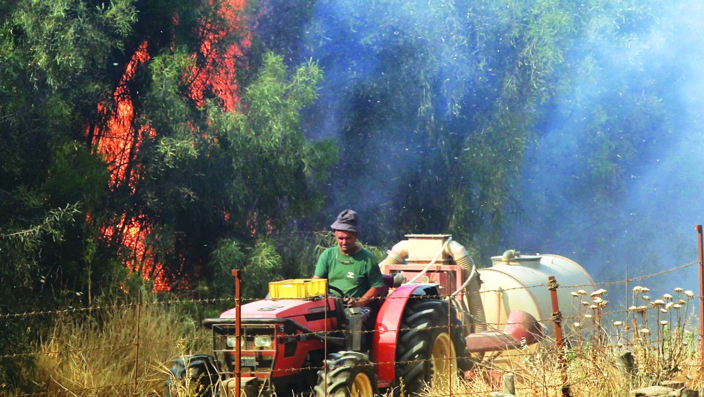 In a blaze that broke out Monday around noon near an IDF base in Beit Guvrin, some 20 firefighting units plus six aircraft were deployed, but not before about 30,000 dunams [nearly 12 square miles] were burned, Ynet reported. The Beit Guvrin fire also spread to Moshav Lachish and police evacuated nearby Park Lachish until the flames were extinguished. (Top) An Israeli firefighter plane tries to extinguish a fire which broke out in Park Lachish near Ashdod on Monday.  (Bottom) Israeli firefighter at the fire in Park Lachish. (Flash90)