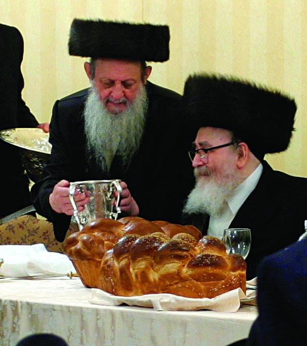 "Reb Shia Friedman, z""l, handing, ybl""c, the Skvere Rebbe, shlita, a pitcher to wash his hands. (JDN)"
