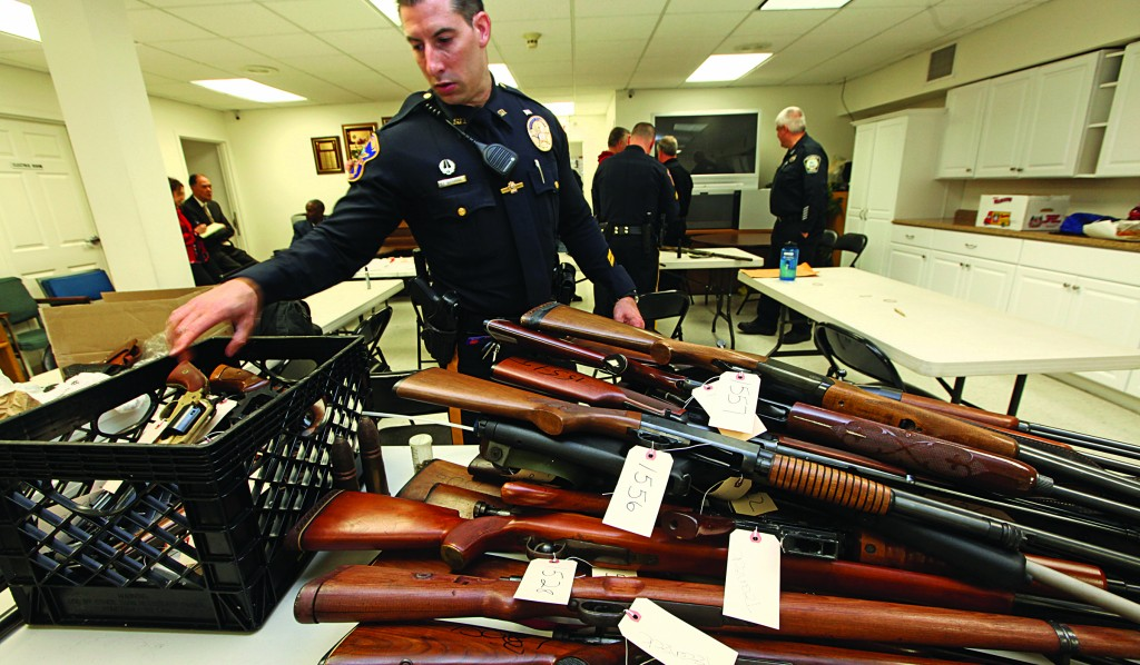 Officer Tom Richards puts another gun on a pile next to a milk crate containing hand guns in Teaneck, N.J., Sunday as part of a gun buyback program. (AP Photo/The Record, Chris Pedota)