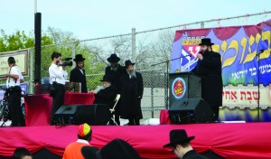 Harav Moshe Wolfson sits on stage before his address at the Gan Yisroel parade in Boro Park.