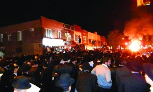 Thousands dance around a bonfire in front of Beis Medrash Karlin Stolin in Boro Park on Motzoei Shabbos.