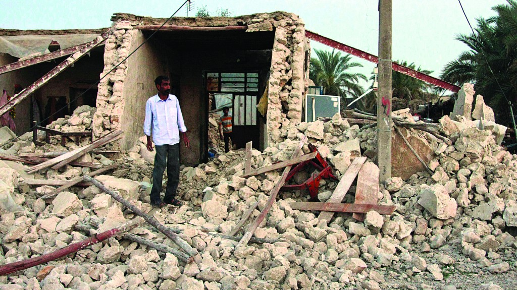 An Iranian man stands among the ruins of buildings after an earthquake struck southern Iran, in Shonbeh, Iran, Tuesday. (AP Photo/Fars News Agency, Mohammad Fatemi)