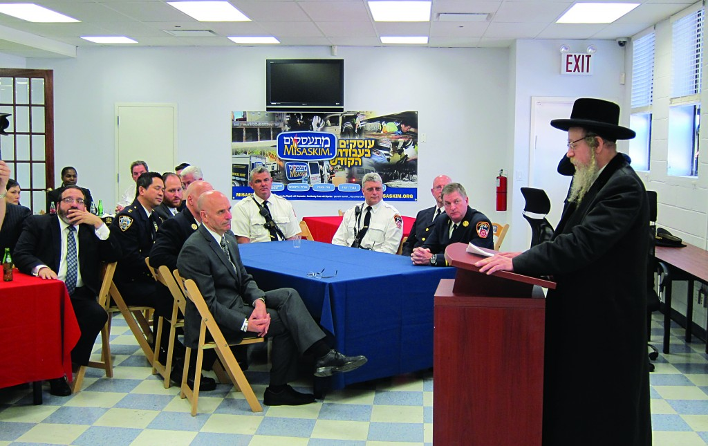 Harav Chanoch Dov Ashkenazi, the Horodenke Rav, addressing police and fire officials at an event Wednesday at the Misaskim headquarters to thank them for saving four sifrei Torah.