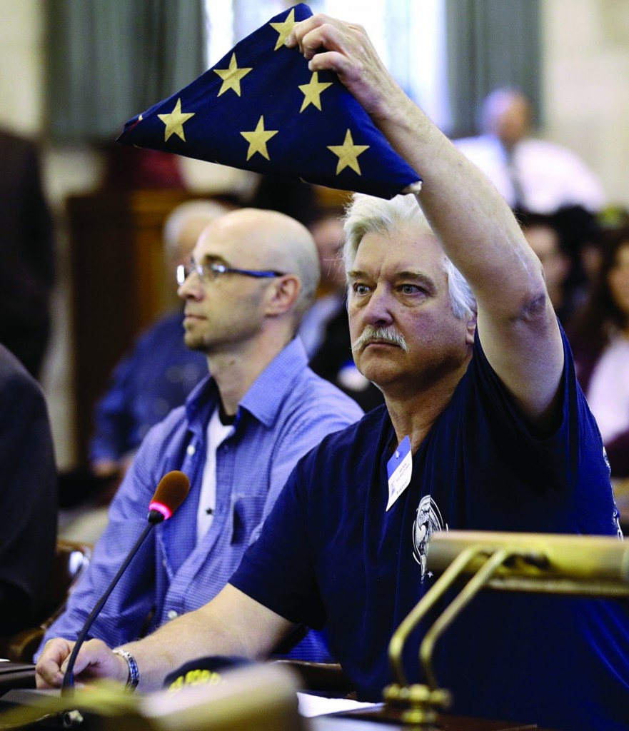 Glenn Darwell, of Forked River, NJ, who is against strict gun laws, holds a U.S. flag while addressing the state legislature during the hearing Tuesday on gun control. (AP Photo/Julio Cortez)
