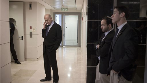 Former Israeli Prime Minister Ehud Olmert talks on a phone near his bodyguards after an interview with The Associated Press in Tel Aviv, Thursday. (AP Photo)