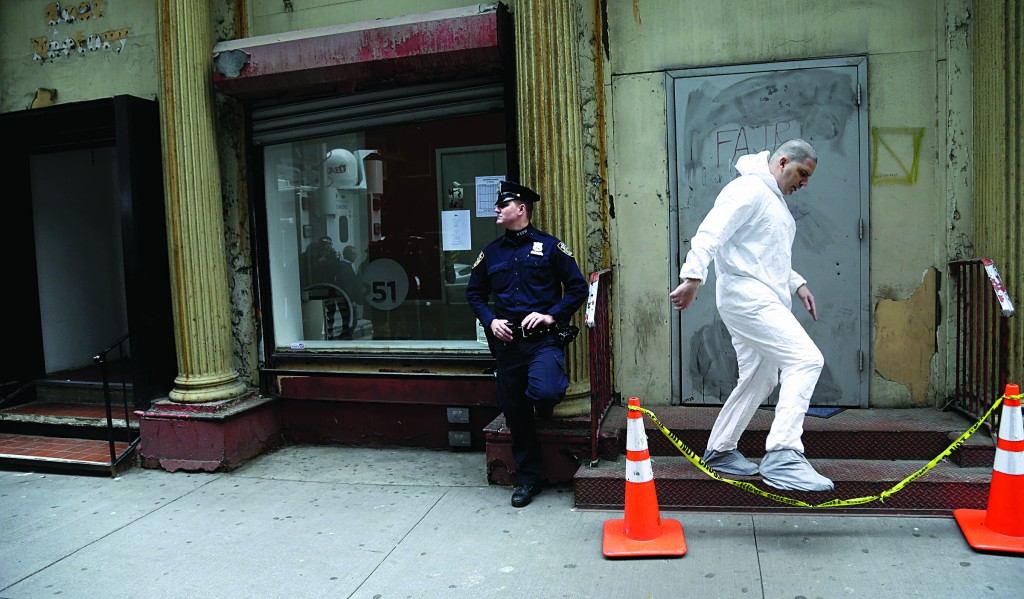An official in a protective suit exits the site Tuesday where a plane part was discovered. (AP Photo/Seth Wenig)