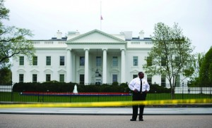 A member of the U.S. Secret Service stands watch on Pennsylvania Ave. in front of the White House after its flag was lowered to half-staff to honor the victims of the attack.