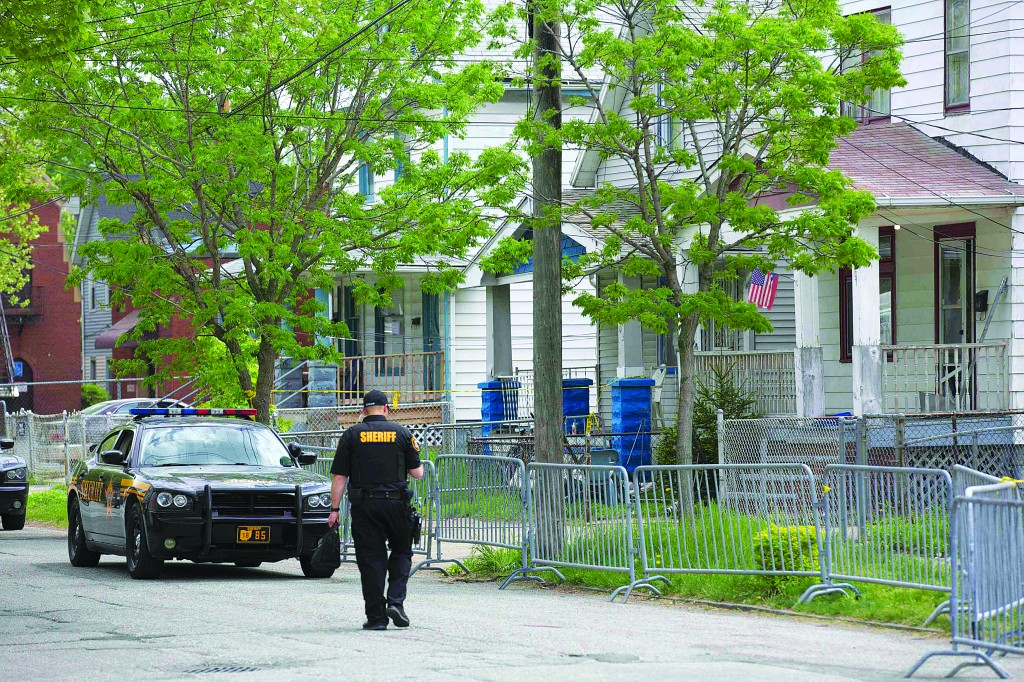 A police officer walks past the house where three women who vanished as teenagers about a decade ago were discovered alive, in Cleveland, Ohio Tuesday.(REUTERS/John Gress)