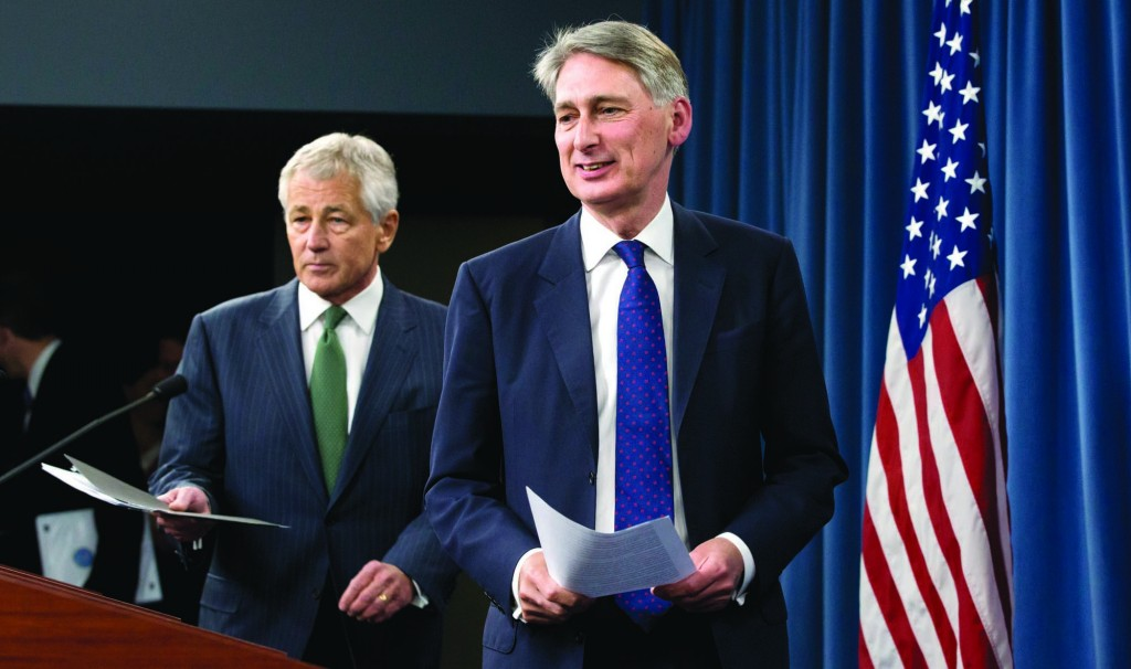 Defense Secretary Chuck Hagel follows British Defense Secretary Philip Hammond to their joint news conference at the Pentagon, Thursday, where they answered questions about Syria. (AP Photo/J. Scott Applewhite)